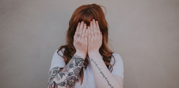 Tattooed woman hiding face | Annie Spratt via Unsplash CC License by